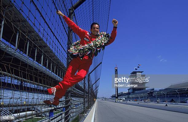 Helio Castroneves of Brazil climbs the fence to celebrate winning the Indy 500 part of the Indy Racing Northern Lights Series at the Indianapolis...