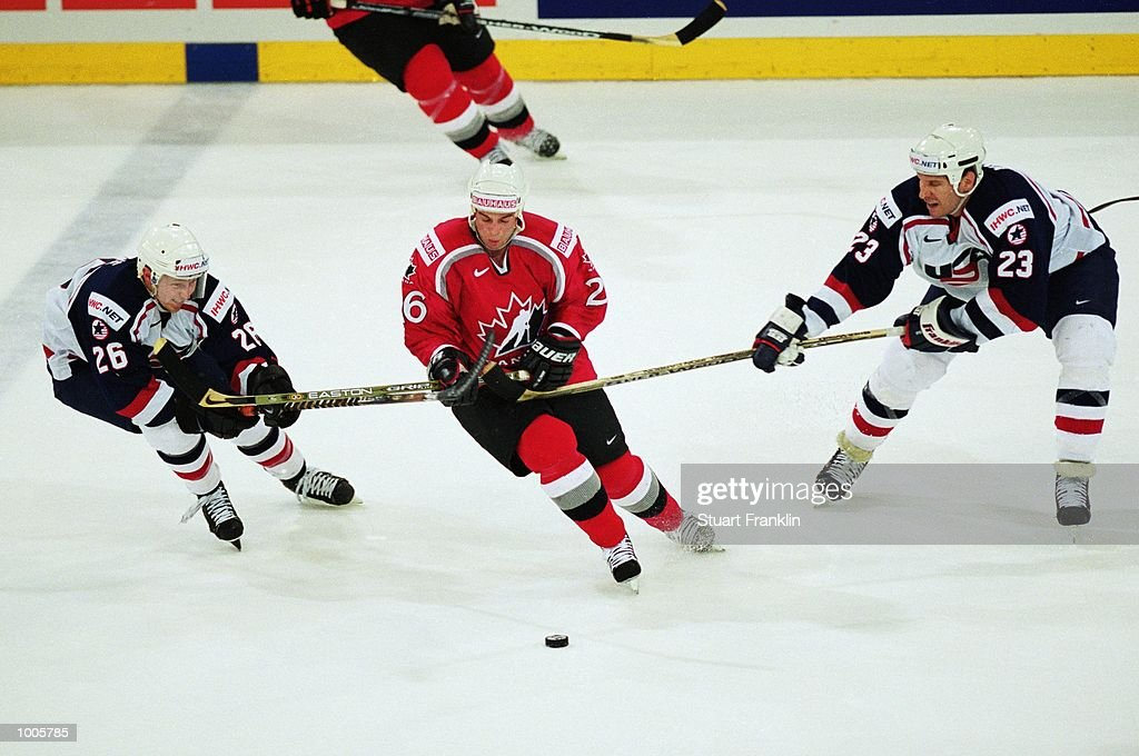 Steve Sullivan of Canada breaks free from USA's Mike Knuble (right) and Derek Plante (left) during the IIHF World Ice Hockey Championship Quater-final match between USA and Canada held at the Preussag Arena in Hanover, Germany. \ Mandatory Credit: Stuart Franklin /Allsport