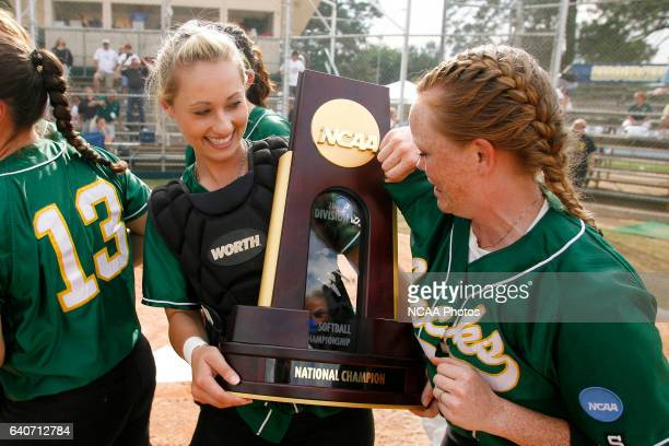 Humboldt State pitcher Hannah Jones polishes the National Championship Trophy with her jersey as teammate Marissa Slattery looks on after winning the...