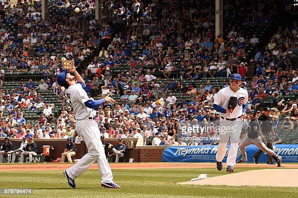 Chicago Cubs third baseman Kris Bryant makes a catch of a Ryan Braun popup as Anthony Rizzo looks on while playing in a baseball game between the...