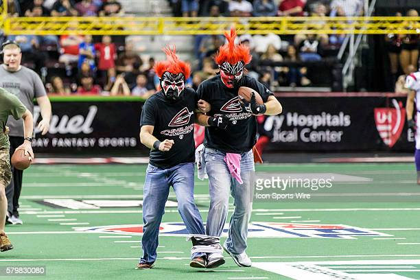 Masked Cleveland Gladiators fans participate in a three legged race during a timeout of the game between the New Orleans VooDoo and Cleveland...
