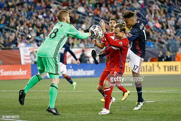 Chicago Fire midfielder Drew Conner glabs the ball as Chicago Fire defender Michael Harrington tries to protect him from New England Revolution...