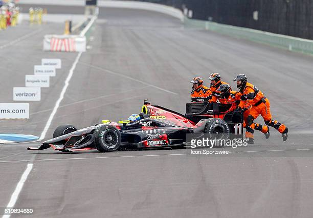 IndyCar driver Sebastien Bourdais receives a much start from the safety crew following an accident during the start of the Angie's List Grand Prix of...