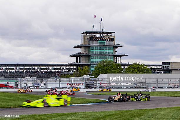 IndyCar driver Simon Pagenaud goes by at speed with the Pagoda in the background during the running of the Angie's List Grand Prix of Indianapolis at...