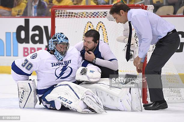 Tampa Bay Lightning goalie Ben Bishop in looked at by the medical trainers after suffering an apparent injury during the first period of Game One in...