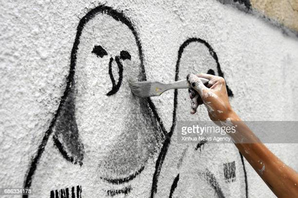 BEIJING May 21 2017 A Yemeni activist draws the graffiti of peace doves on the wall in a street in Sanaa capital of Yemen on May 14 2017 Yemeni...