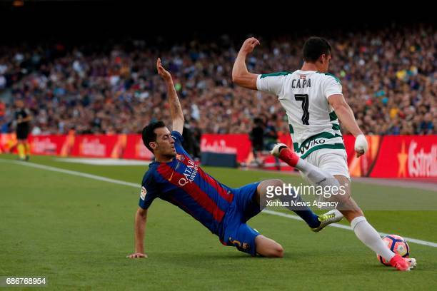 Barcelona's Sergio Busquets vies with Eibar's Capa during the Spanish first division soccer match at the Camp Nou Stadium in Barcelona Spain May 21...