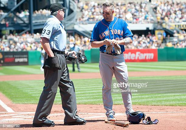 New York Mets left fielder Michael Cuddyer talks with umpire Mike Winters after striking out to end the first inning in the game between the New York...