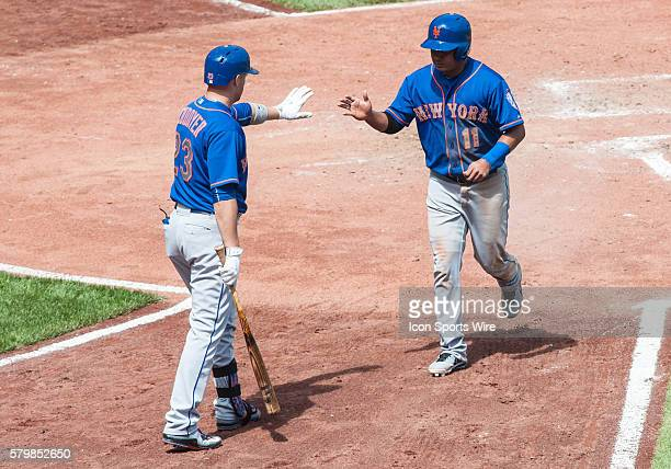 New York Mets shortstop Ruben Tejada is greeted by first basemen Michael Cuddyer after scoring on a single by shortstop Wilmer Flores during the...
