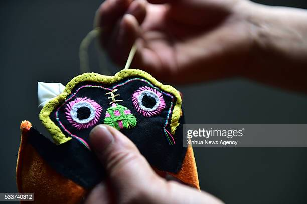 Luo Jihua makes a tigerhead shoe in Bengbu City east China's Anhui Province May 20 2016 Ding Yuan and Luo Jihua a couple who are inheritors of...