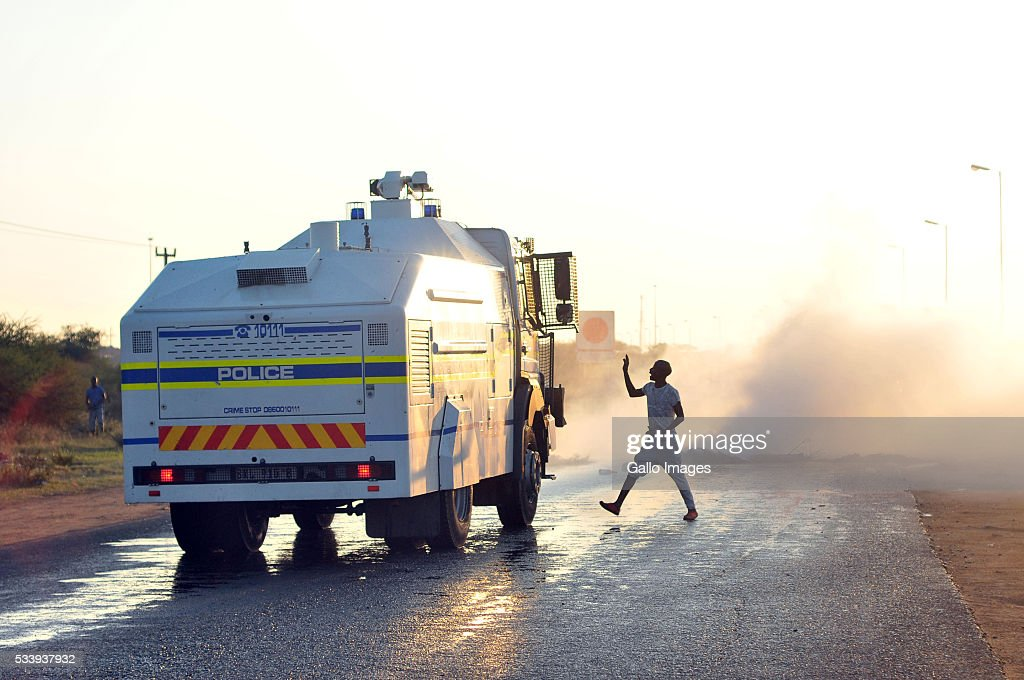 A man confronts a police vehicle as its water cannon extinguishes a fire blockading a road during a protest against evictions in Hammanskraal on May 23, 2016 in Pretoria, South Africa. At least two people died, while others were assaulted.