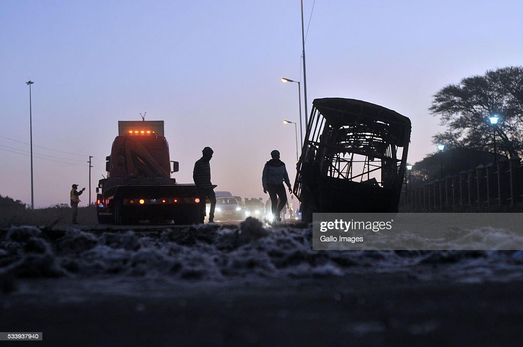 Burnt out buses used as blockades are moved to allow traffic through during protests against evictions in Hammanskraal on May 23, 2016 in Pretoria, South Africa. At least two people died, while others were assaulted.