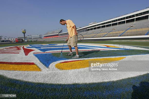 May 25 2006 Charlotte NC USA Ethan Miller paints the infield logos on the grass during Nextel Cup practice and qualifying for the CocaCola 600 at...