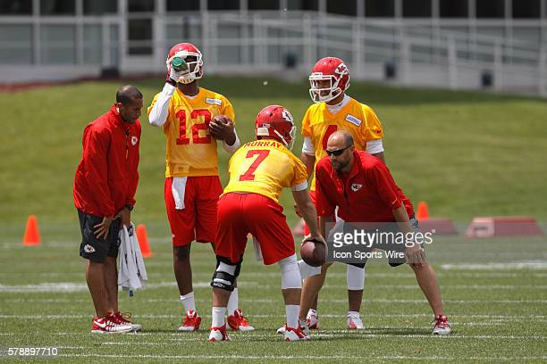 Quarterback Aaron Murray practices dropping back as Terrance Owens and Jonathon Jennings look on during the Kansas City Chiefs rookie minicamp at the...