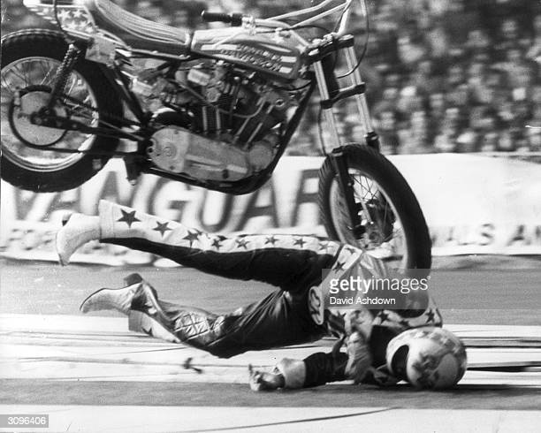 American stuntman Evel Knievel clears a row of thirteen singledeck buses on his motorbike only to crash on the landing ramp at Wembley Stadium London...