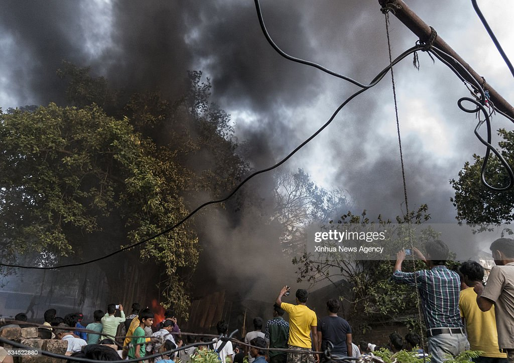 People gather at a factory which is on fire in south Kolkata, capital of eastern Indian state West Bengal, on May 26, 2016. No casualty was reported so far in the fire at the factory on Thursday.