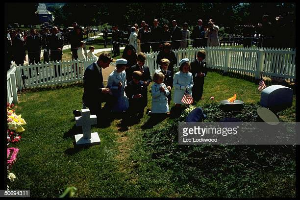 Kneeling in prayer at grave site of slain President on first birthday after assassination brother Robert F Kennedy w his children Jacqueline Kennedy...