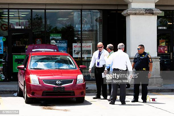 Sheriff officer's exam a crime scene leaving one person in the red Nissan dead in the North Shore suburb of Houston