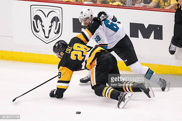 San Jose Sharks right wing Melker Karlsson and Pittsburgh Penguins defenseman Ian Cole fall to the ice as puck slides away during the San Jose Sharks...