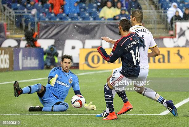 Los Angeles Galaxy goalkeeper Jaime Penedo makes the save as Los Angeles Galaxy defender Omar Gonzalez angles off New England Revolution midfielder...