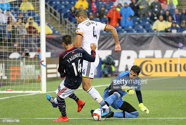 Los Angeles Galaxy goalkeeper Jaime Penedo stops the ball as Los Angeles Galaxy defender Omar Gonzalez guides New England Revolution midfielder Diego...