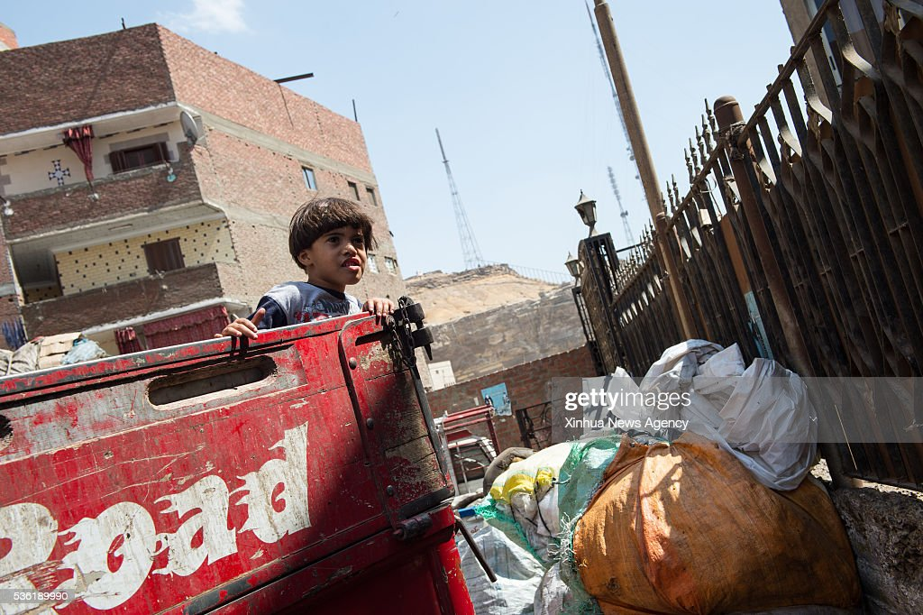 CAIRO, May 31, 2016-- A boy stands on a truck carrying garbage at the Al-Mokattam City, also known as the 'Garbage City', in Cairo, capital of Egypt, on May 27, 2016. Living on the outskirts of Cairo, the Zabalen, which literally means 'garbage people', is a community that has been collecting and recycling Cairo's waste for a long time. They collected and sorted the waste for a living at Al-Mokattam City. The children here live and play among the garbage and lots of them have dropped out of school to help their family's garbage business.