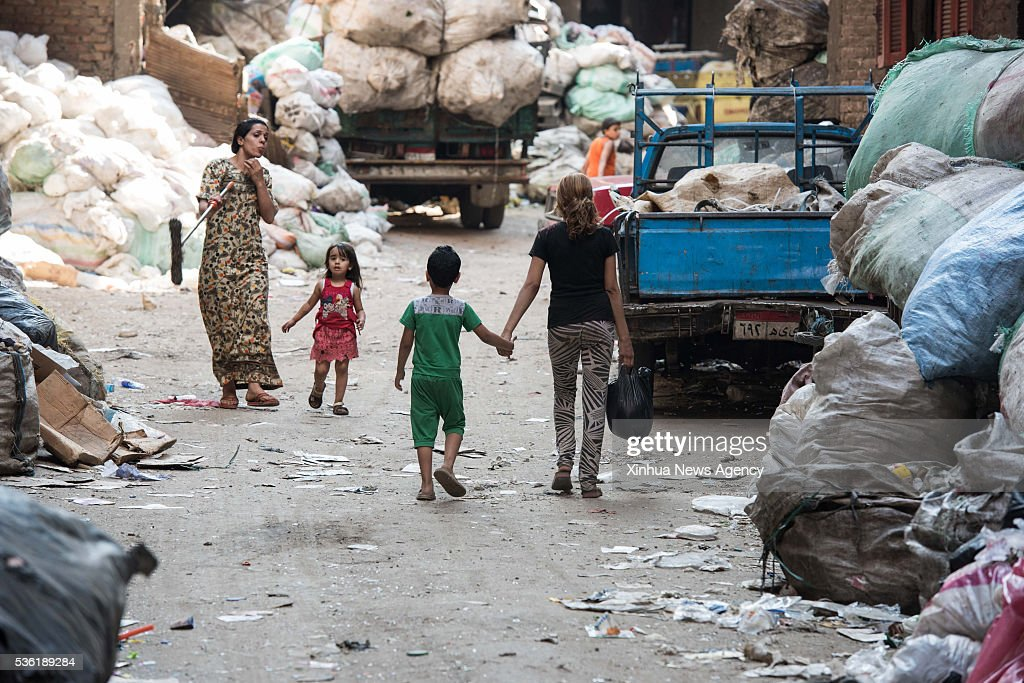 CAIRO, May 31, 2016 -- Children walk in an alley with adults at the Al-Mokattam City, also known as the 'Garbage City', in Cairo, capital of Egypt, on May 27, 2016. Living on the outskirts of Cairo, the Zabalen, which literally means 'garbage people', is a community that has been collecting and recycling Cairo's waste for a long time. They collected and sorted the waste for a living at Al-Mokattam City. The children here live and play among the garbage and lots of them have dropped out of school to help their family's garbage business.