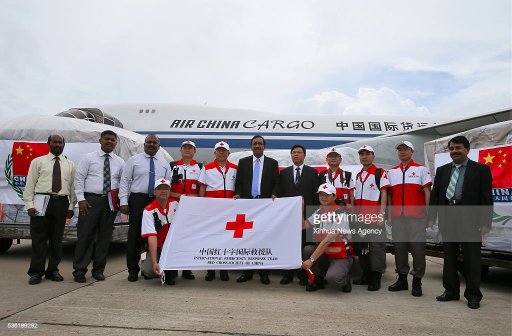 COLOMBO, May 31, 2016 -- Chinese Ambassador to Sri Lanka Yi Xianliang, fifth right rear, Sri Lanka's Minister of Disaster Management Anura Priyadarshana Yapa, center rear, pose for a group photo with members of China's rescue team and staff from Sri Lanka in Colombo, Sri Lanka, May 31, 2016. China on Tuesday handed over a consignment of emergency relief supplies donated to the Sri Lankan government at the country's main airport.