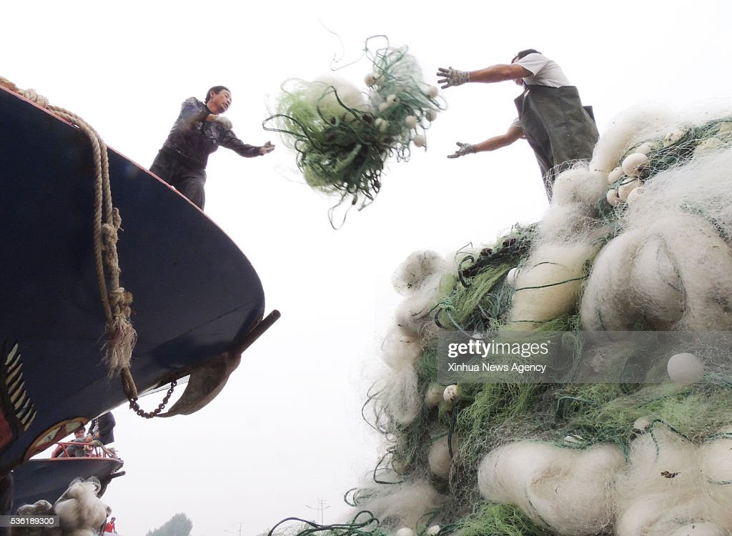 LIANYUNGANG, May 31, 2016 -- Fishermen settle the fishing net in the harbour in Lianyungang City, east China's Jiangsu Province, May 31, 2016. Annual fishing ban will start from June 1 on China's Yellow Sea, Bohai Sea and the East China Sea.
