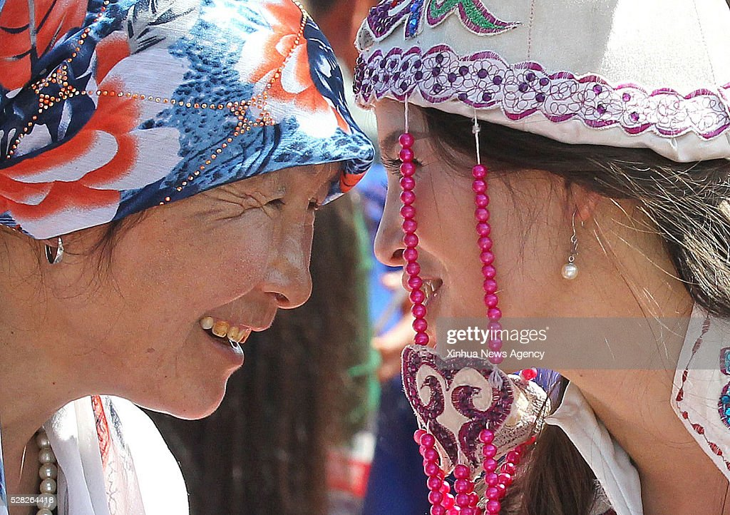 HAMI, May 4, 2016 -- A mother, left, blesses her daughter at a group wedding ceremony in Hami City, northwest China's Xinjiang Uygur Autonomous Region, May 4, 2016. Altogether 60 couples attended a group wedding ceremony in Hami on May 4, China's National Youth Day.