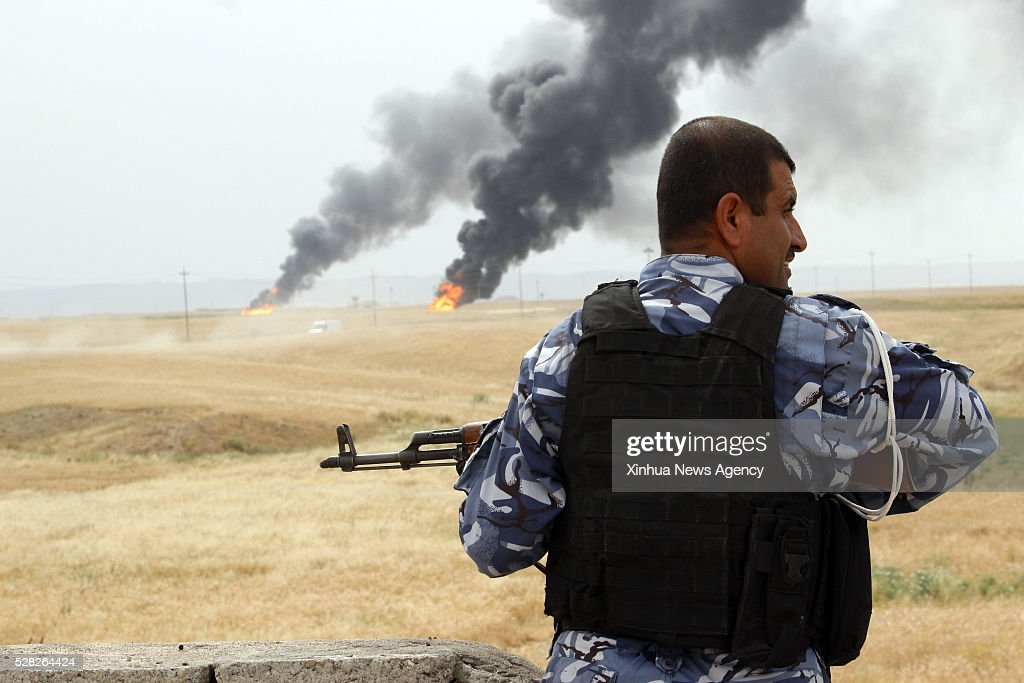 KIRKUK, May 4, 2016-- A security force member looks at Khabbaz oil fields in the southwest of Kirkuk, Iraq, May 4, 2016. The fields were attacked by unidentified gunmen on Tuesday evening.
