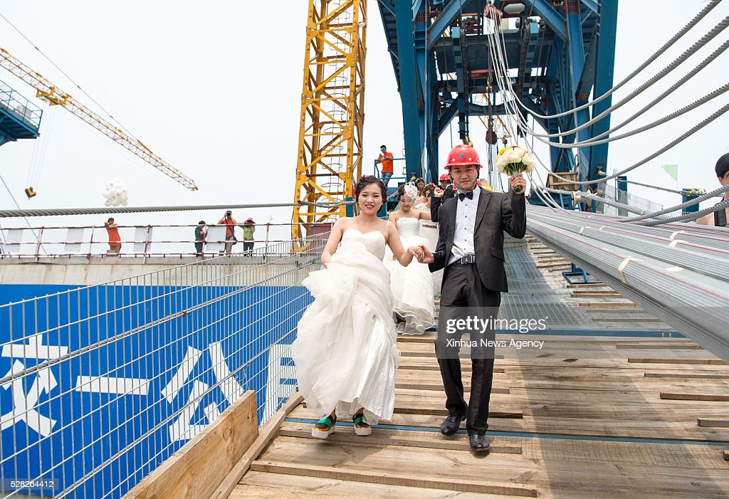 CHONGQING, May 4, 2016 -- Young couples walk up to have their wedding photos taken on a suspension bridge over the Yangtze River in southwest China's Chongqing Municipality, May 4, 2016. Eight pairs of new couples took part in the theme party to celebrate their love on China's National Youth Day over the suspension bridge with the longest span of over 1,000 meters in the upper reaches of Yangtze River here in Chongqing.