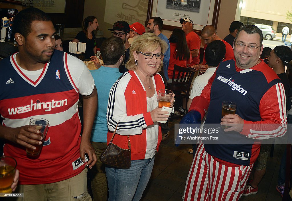 Ryan Sabo, right, his wife Kim Sabo, and Alan Day, dressed in proper attire, enjoy a beer before watching a Wizards playoff game at the Verizon Center.