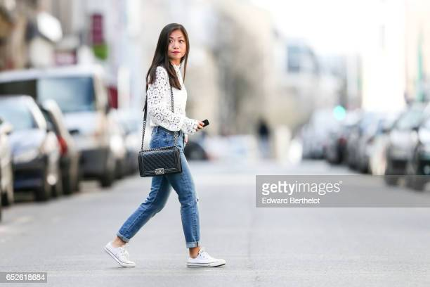 May Berthelot Head of Legal at Videdressingcom and fashion blogger wears a Lovie Co white lace top The Kooples blue denim jeans pants Converse white...
