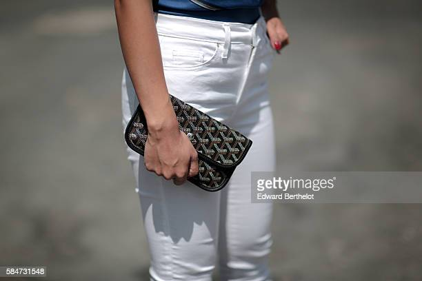 May Berthelot is wearing a Hermes Vif Argent blue scarf as a top Topshop white jeans pants Triwa sunglasses Asos sandals and a Goyard clutch during a...