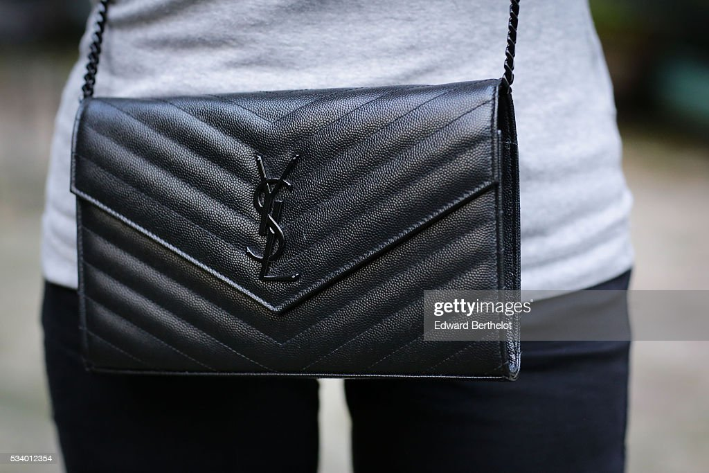 May Berthelot (@maymaryb), is wearing a Saint Laurent YSL black clutch bag, during a street style session, on May 24, 2016 in Paris.