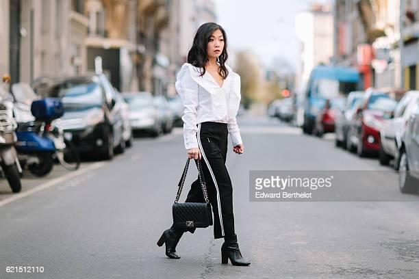 May Berthelot is wearing a Zara white ruffle top Zara black pants with white stripes a Chanel black Boy bag and Zara black boots on November 6 2016...
