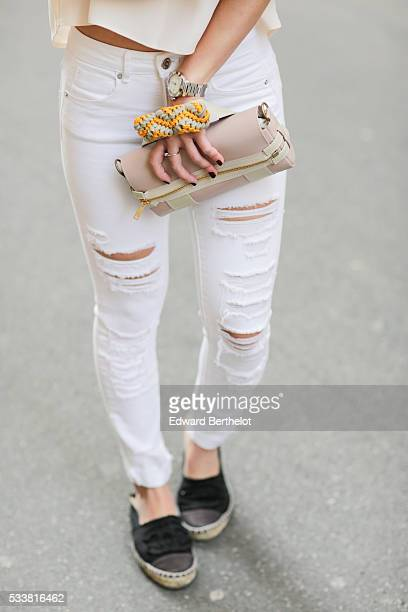 May Berthelot is wearing Chanel black espadrilles shoes Zara white ripped jeans a Topshop nude Bardot top and a Darris pink bag during a street style...