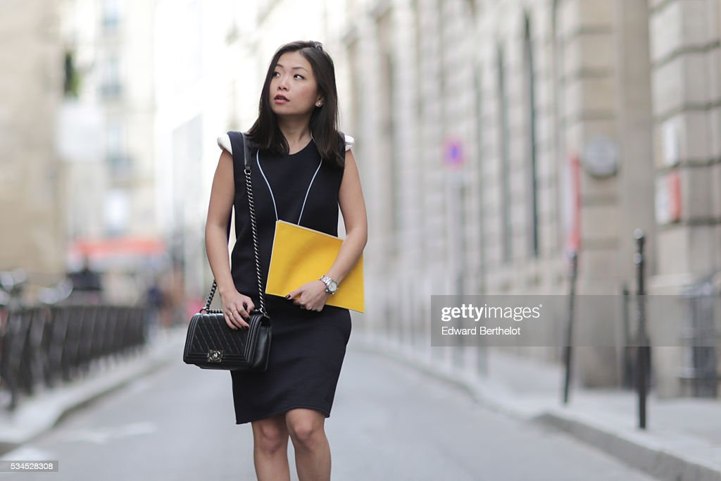 May Berthelot (@maymaryb), is wearing Darris yellow clutch bag, an Iris Cantabri dress, a black Chanel Boy bag, and Asos sandals, during a street style session, on May 26, 2016 in Paris.