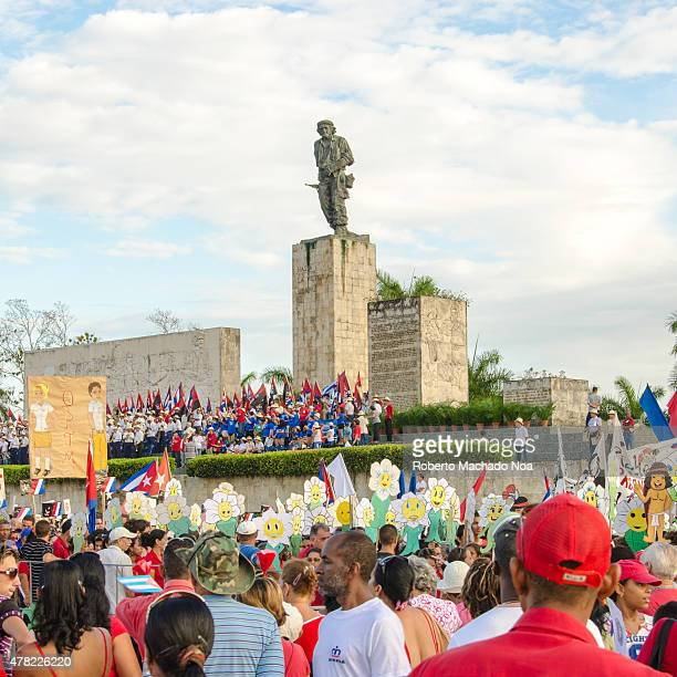 May day celebration in Cuba Che Guevara Statue with a crowd standing in the front wearing red white and blue holding smiley face signs