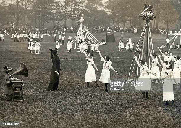 May Day festivities A group of women dance next to a Maypole to the tunes of a phonograph set up on a chair Undated photograph circa 1900