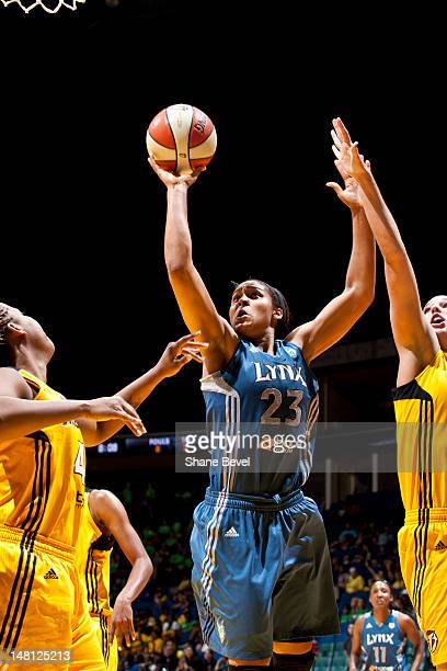 Maya Moore of the Minnesota Lynx drives past Kayla Peterson and Amber Holt of the Tulsa Shock during the WNBA game on July 10 2012 at the BOK Center...