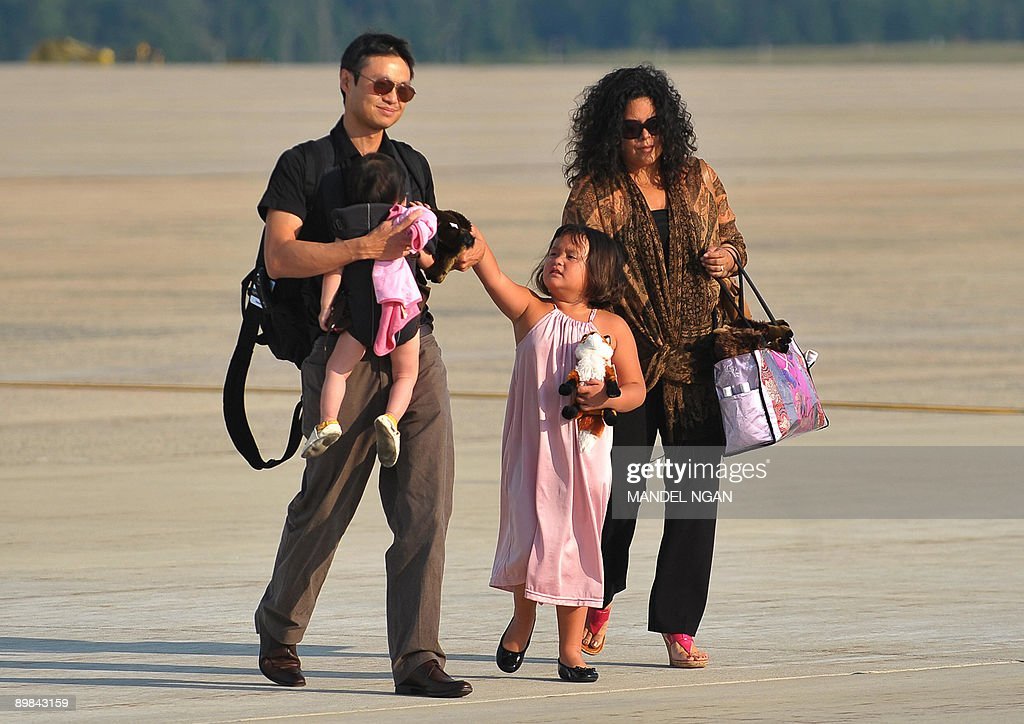 <a gi-track='captionPersonalityLinkClicked' href=/galleries/search?phrase=Maya+Soetoro-Ng&family=editorial&specificpeople=5417496 ng-click='$event.stopPropagation()'>Maya Soetoro-Ng</a>, a sister of US President Barack Obama, and her husband Konrad Ng with their children Suhalia (2nd R) and Sevita (L) walk on the tarmac at Andrews Air Force Base in Maryland. US President Barack Obama and his family returned to Washington after a weekend visit to Montana, Wyoming, Colorado and Arizona. AFP PHOTO/Mandel NGAN