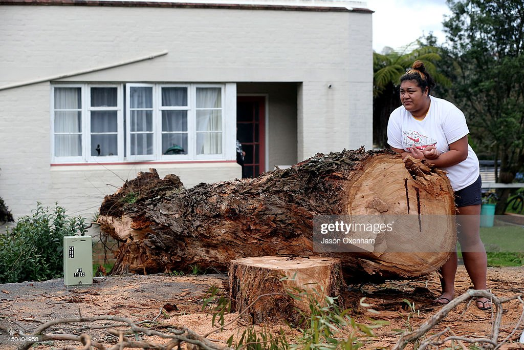 Maya Tafutu leans on the fallen tree outside her house on Great North Road, Western Springs on June 11, 2014 in Auckland, New Zealand. Tafutu watched the tree luckily fall away from her house onto the road at 1:30am. Cyclonic winds and heavy rainfall has caused damage across Auckland, Northland and Waikato. Storms resulted in wide ranging power outages and property damage.