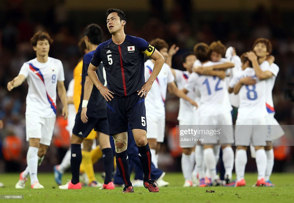 Maya Yoshida of Japan looks dejected as Korea players celebrate defeating Japan during the Men's Football Bronze medal play-off match between Korea and Japan on Day 14 of the London 2012 Olympic Games at Millennium Stadium on August 10, 2012 in Cardiff, Wales.