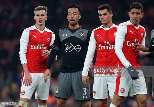 Maya Yoshida of Southampton stands between Rob Holding Granit Xhaka and Gabriel Paulista of Arsenal during the EFL Quarter Final Cup match between...