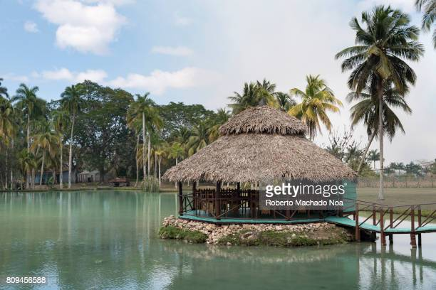 Mayajigua Lakes Round restaurant tiki hut on a stone platform in a lake in front of a palm grove