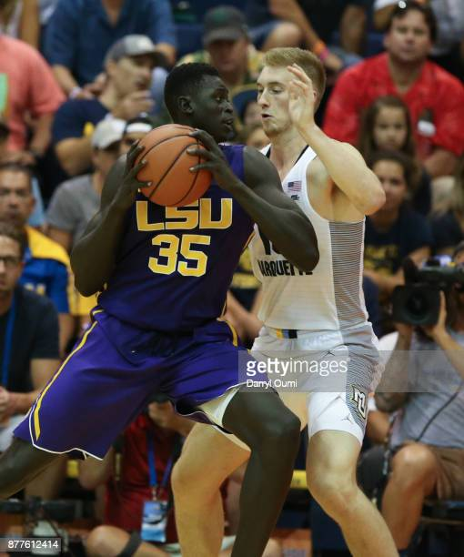 Mayan Kiir of the LSU Tigers is guarded by Sam Hauser of the Marquette Golden Eagles as he makes a move to the basket during the first half of their...
