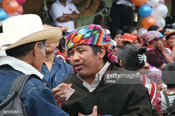 Mayan men bargaining  at the marketplace in village Chichicastenango, Guatemala