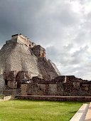 Mayan step pyramid and temple ruins against cloudy sky